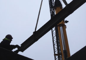 A worker moving a metal beam.